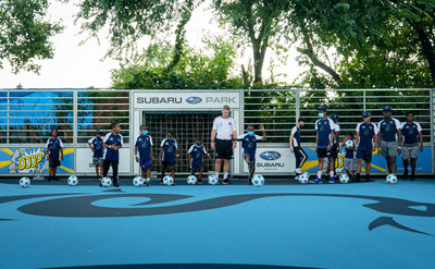 Philadelphia Union's Youth Director of Coaching, Phil Griffiths, and children from YMCA of Greater Philadelphia's Soccer for Success program, kick off the ceremonial first kick at the unveiling of the new Subaru Park Camden Mini-Pitch located in Camden, New Jersey, the home of Subaru of America, Inc.